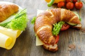 Croissant sandwich with cheese and vegetables for healthy snack, rustic wooden background